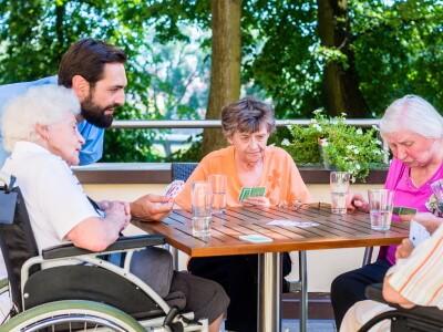 Senioren mit Betreuer sitzen auf einer Terrasse und spielen Karten