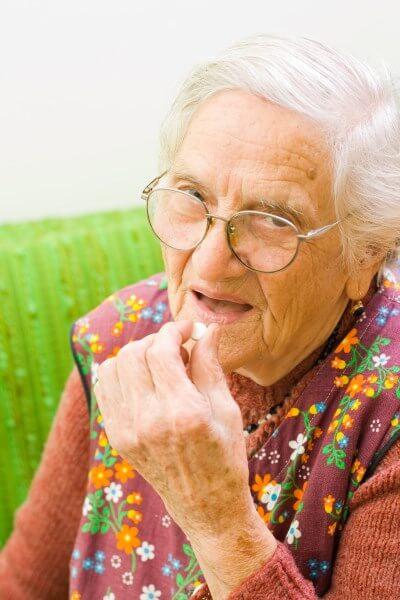 Alte Dame nimmt Medikament ein
