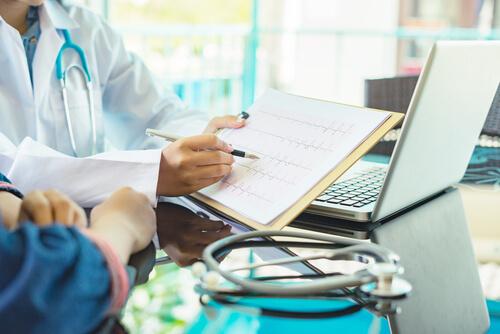 Arzt zeigt Ergebnis Elektrokardiogramm