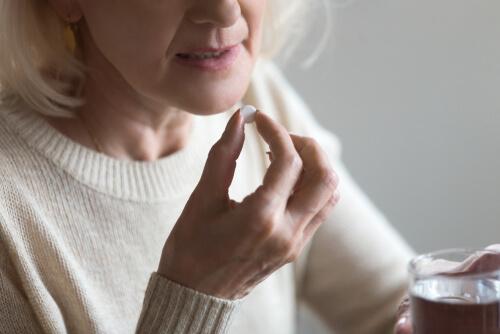 Ältere Frau nimmt Tablette mit Wasser ein