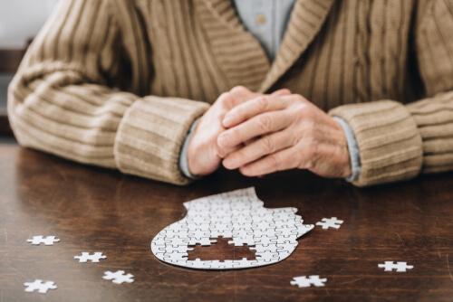 Mann sitzt vor einem Puzzle, das die Form eines Gehirns hat