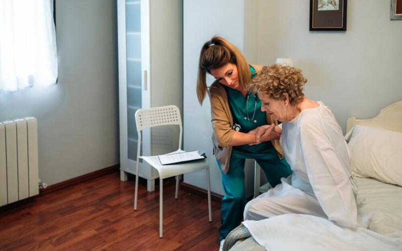 Krankenschwester hilft Patientin beim Aufstehen