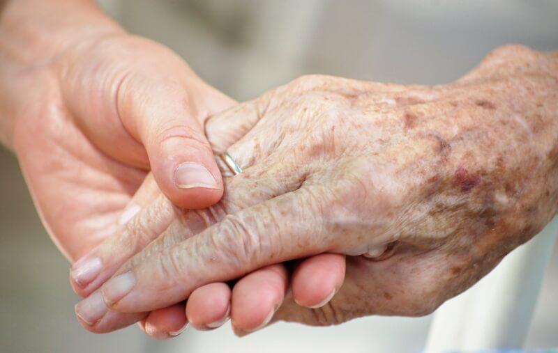 Pfleger reicht älterem Menschen mit Pflegebedarf die Hand