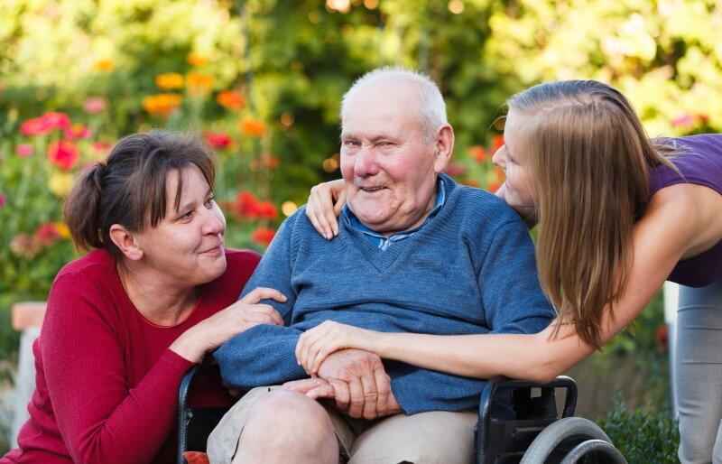 Verhinderungspflege: Ein alter Mann im Rollstuhl ist von zwei jüngeren Frauen umgeben.