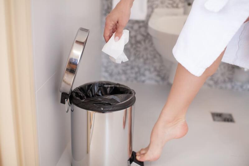 Eine Hand legt ein benutztes Taschentuch in einen Abfalleimer