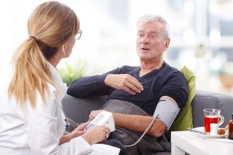 Pflegeberatung durch Pflegedienst: Pflegebedienstete misst Blutdruck im Gespräch mit Patienten