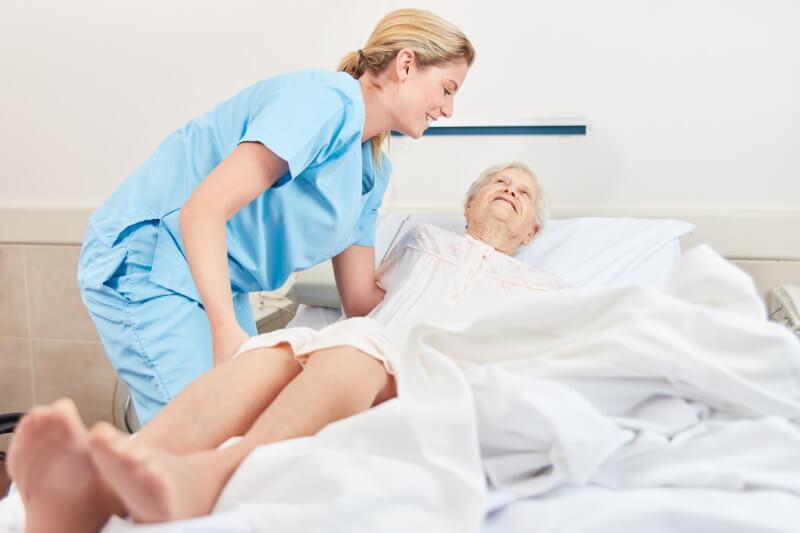 Eine alte Frau wird in einem Krankenbett gepflegt