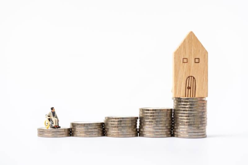 Leibrente als symbolhafte Darstellung: Ein Mensch im Rollstuhl blickt auf ein Haus auf einem Stapel von Geldmünzen