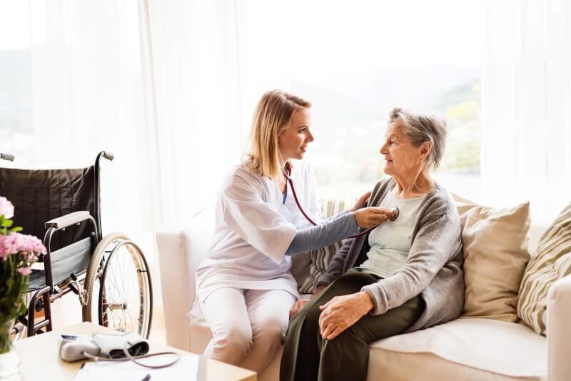 Pflegedienst: Pflegekraft untersucht Betroffenen im häuslichen Umfeld