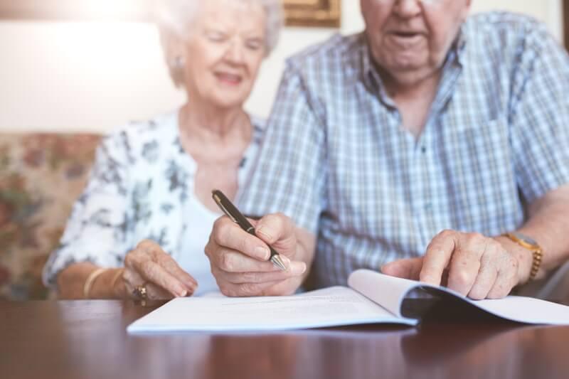 Testament: Älteres Ehepaar unterzeichnet gemeinsam ein Dokument