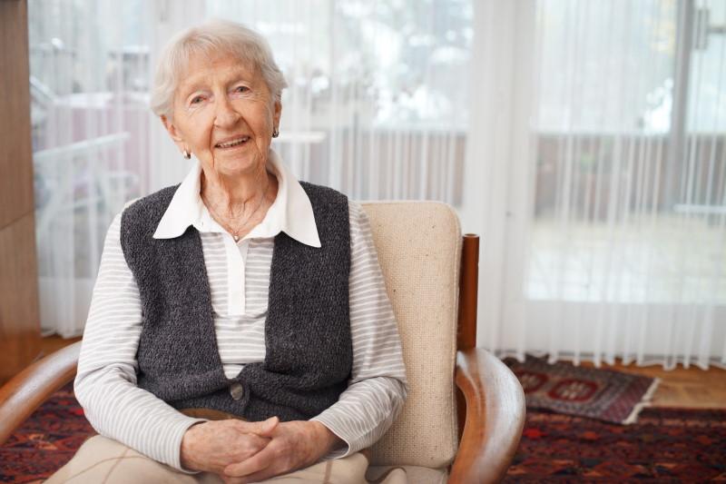 Alte Dame im Sessel schaut zufrieden