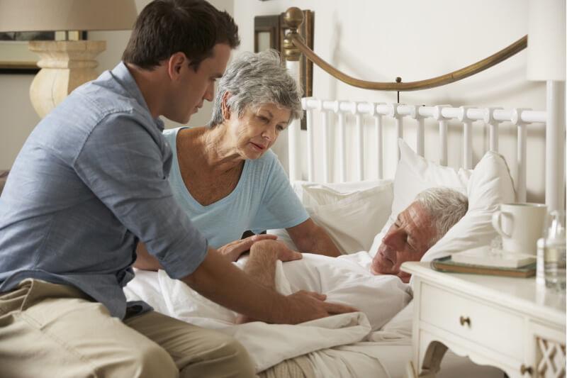 Ein alter Mann liegt in seinem Bett. Familienangehörige schauen besorgt