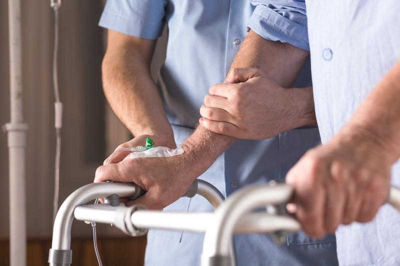 Pflegefinanzierung: Ein Pfleger unterstützt einen Betroffenen