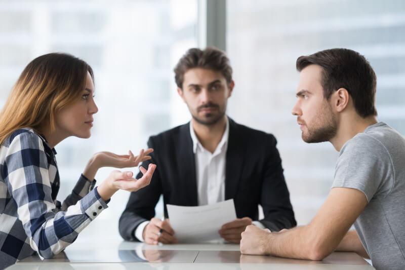 Ein streitendes Ehepaar mit einem Anwalt in der Mitte.
