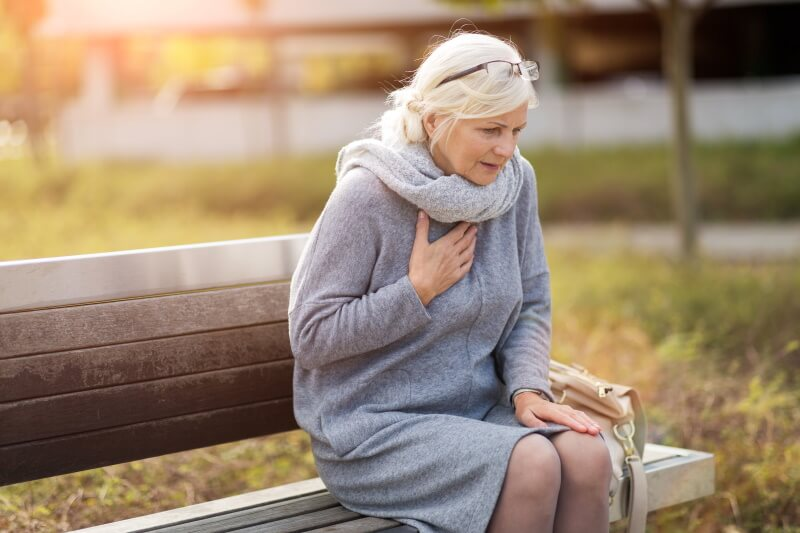 Herzinfarkt: Frau fasst sich auf einer Parkbank in Herzgegend an die Brust