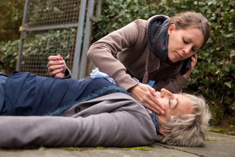 Herzinfarkt: Frau liegt am Boden, eine junge Frau ruft Notarzt mit dem Handy