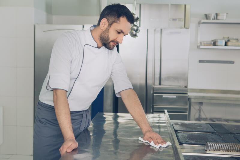 Ein Koch wischt seinen Arbeitsbereich