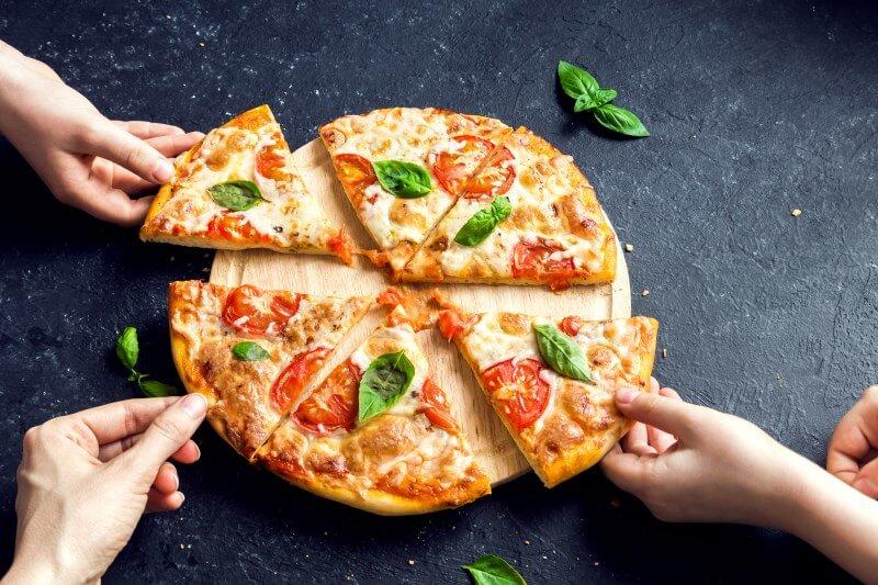 Pflichtteilsanspruch: Mehrere Hände greifen nach Stücken einer Pizza