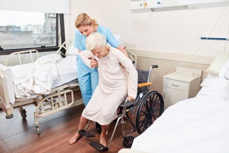 Alte Dame wird aus dem Krankenbett in den Rollstuhl gehoben