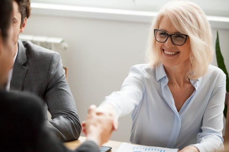 Unternehmensnachfolge: Eine Geschäftsfrau reicht ihrem Verhandlungspartner die Hand
