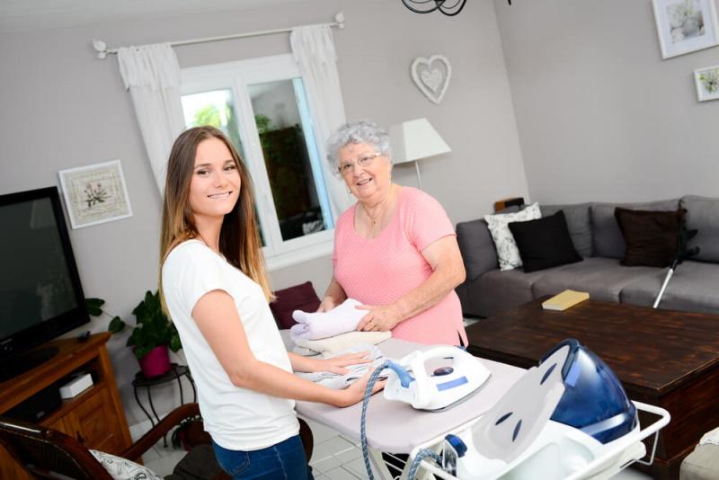 Seniorin bekommt Hilfe beim Bügeln