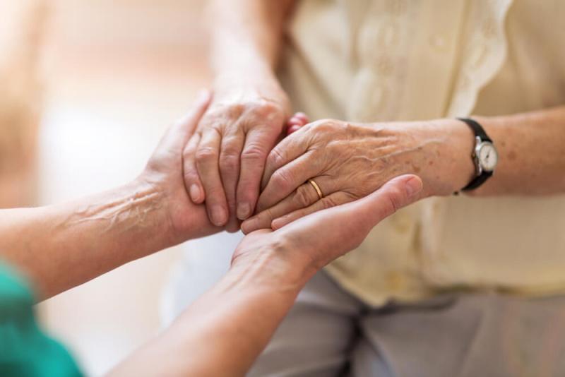 Pllegerin hält Hand von Seniorin