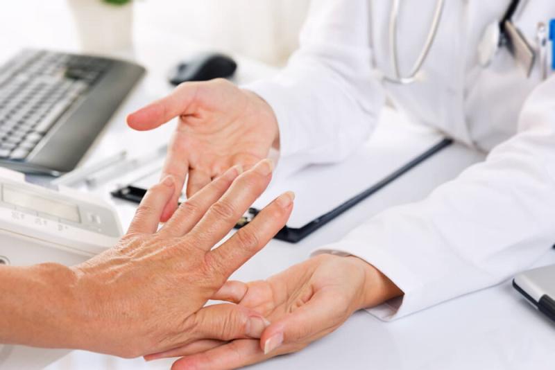Arzt untersucht Gelenk bei Verdacht auf Arthritis