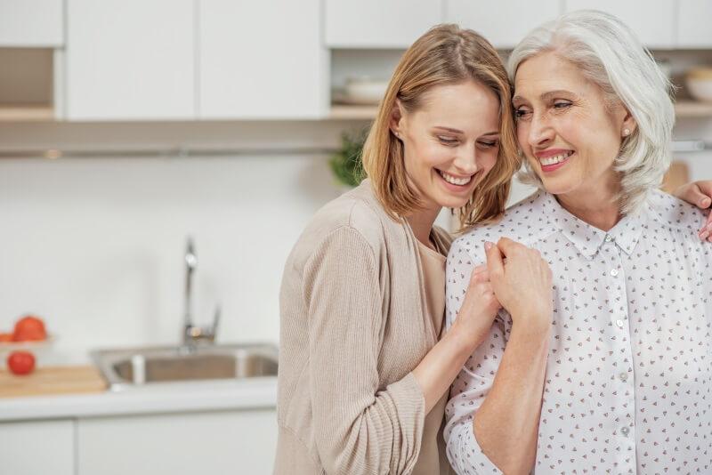 Mutter und Tochter umarmen sich in der Küche