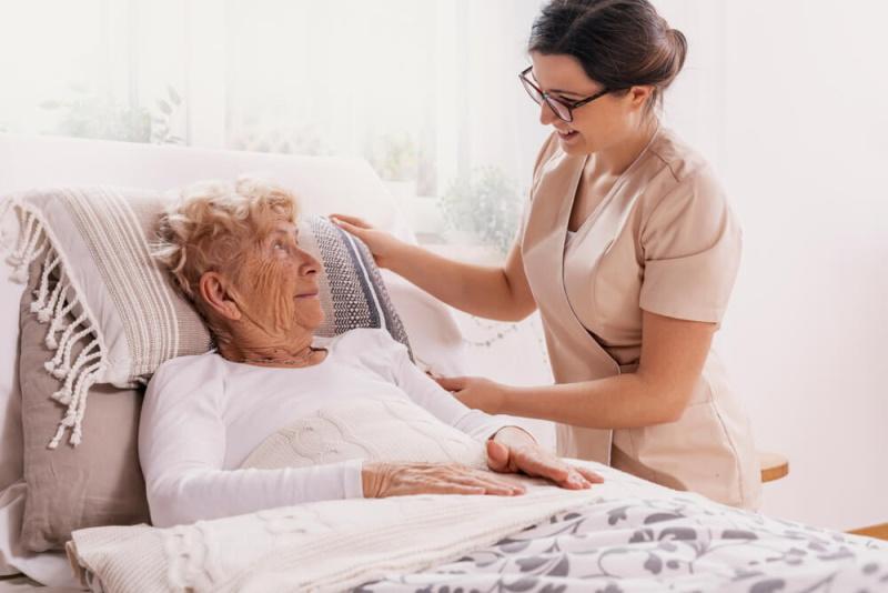Rentnerin sitzt im Bett