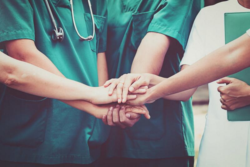 Auszubildende Pflegekräfte halten ihre Hände aufeinander