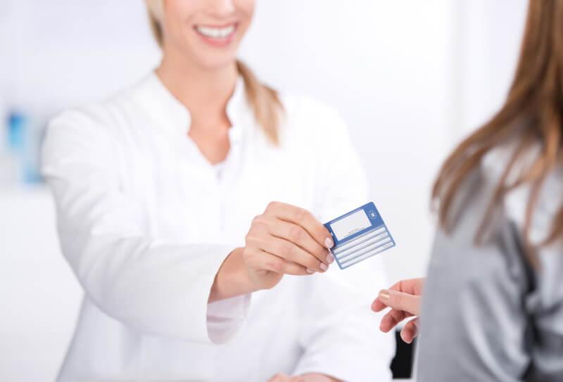 Ärztin reicht Versicherungskarte an Patientin