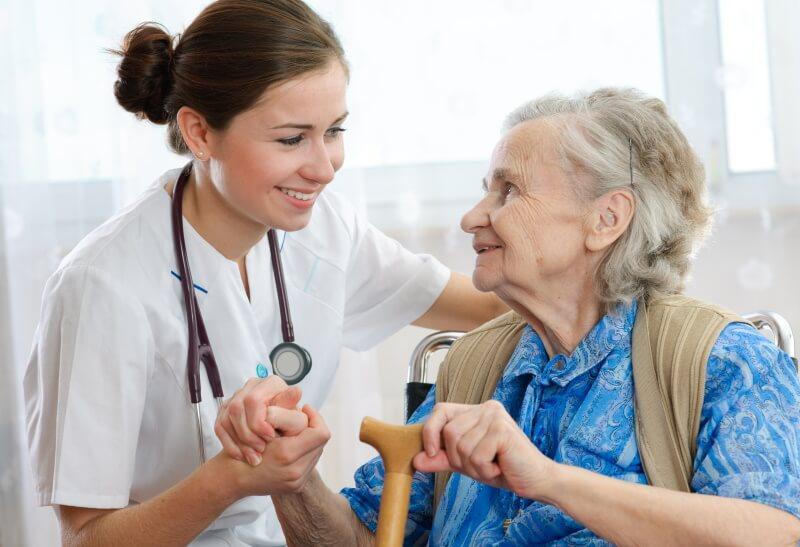 Eine junge Ärztin hält einer älteren Dame die Hand