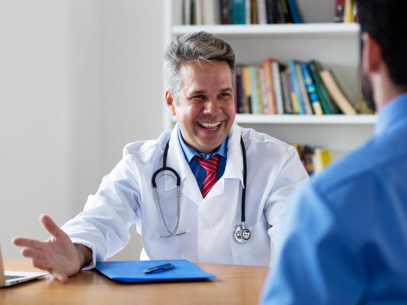 Fröhlicher Arzt berät Patienten mit privater Krankenversicherung.