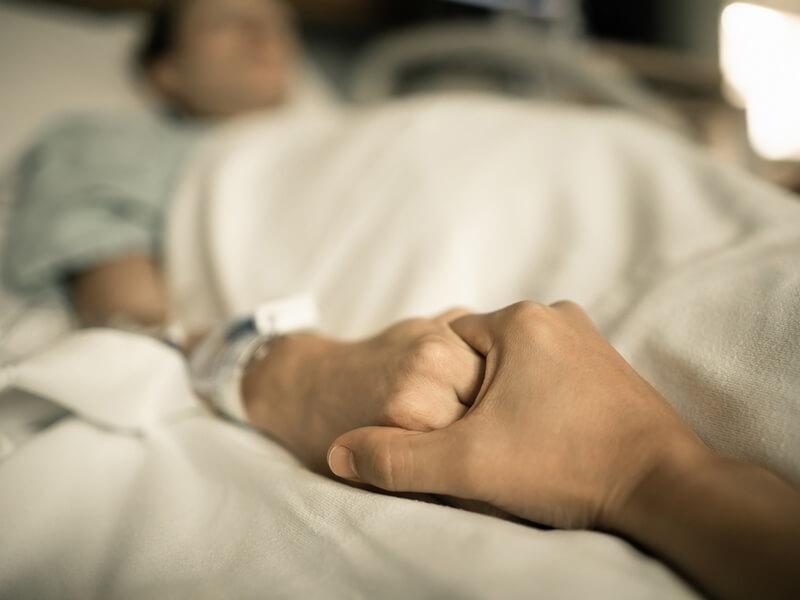 Hand hält die Hand eines Patienten im Krankenhaus