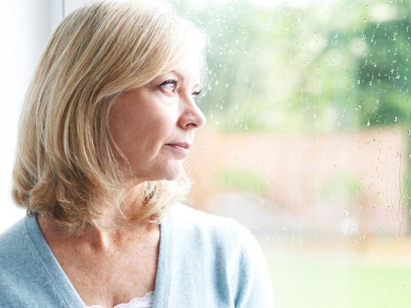 Blonde Frau blickt durch eine Fensterscheibe mit Regentropfen