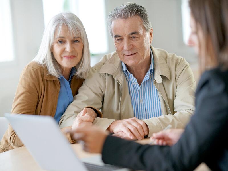 Alteres Paar schaut bei einer Beratung auf einen Laptop