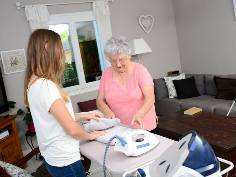 Junge Frau hilft alter Dame beim Bügeln