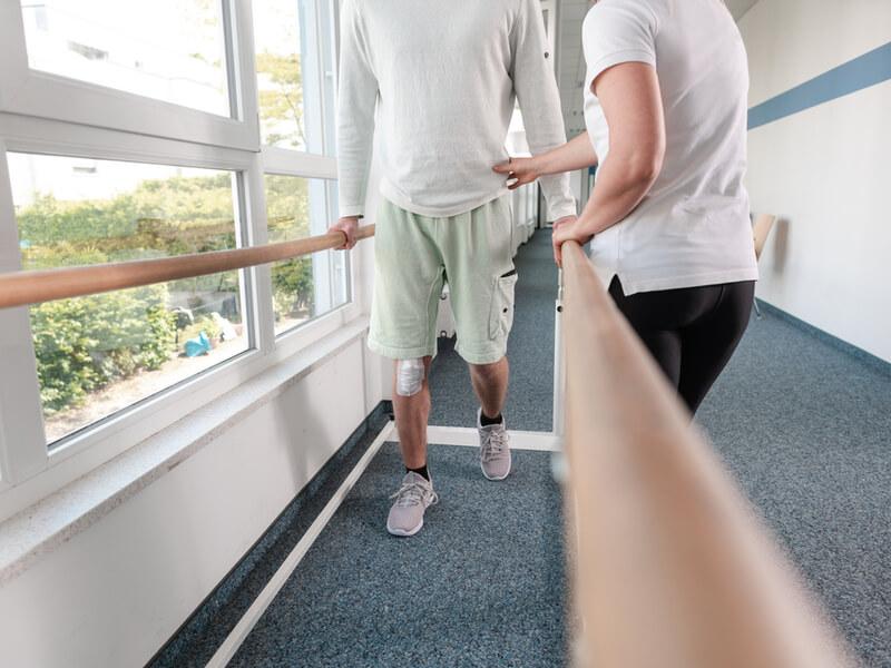 Patient macht Gehübungen mit Hilfe einer Physiotherapeutin