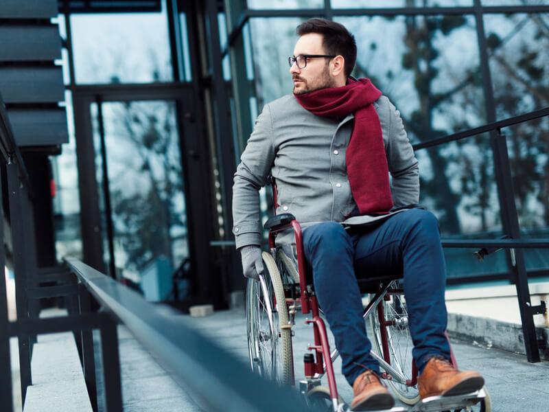 Junger Mann im Rollstuhl vor einem Gebäudeeingang