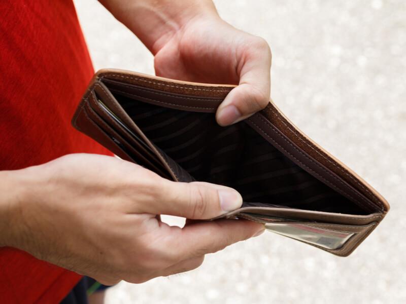 Hände eines Mannes, die ein leeres Portemonnaie halten