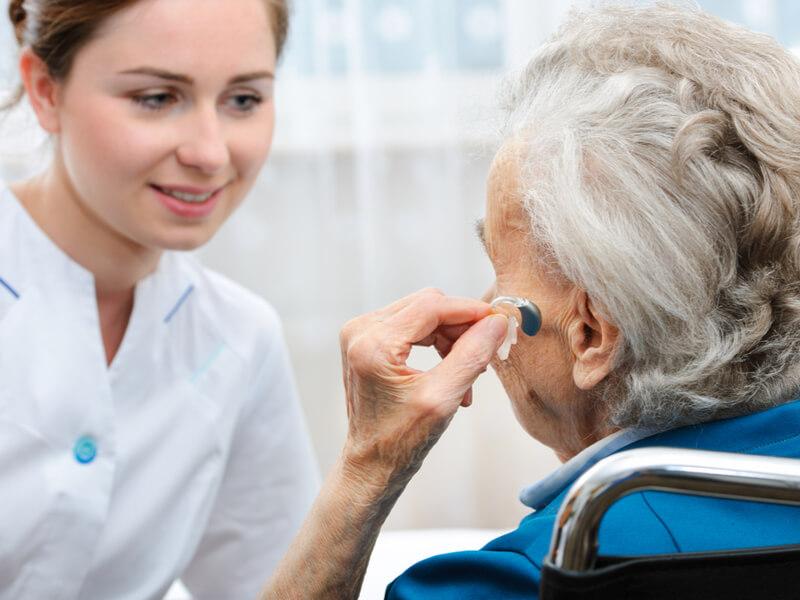 Alte Dame setzt unter Beaufsichtigung einer Pflegerin Hörgerät ein