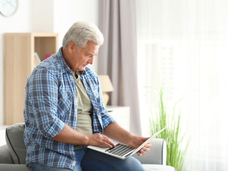 Älterer Mann mit Laptop sitzt auf einem Sessel