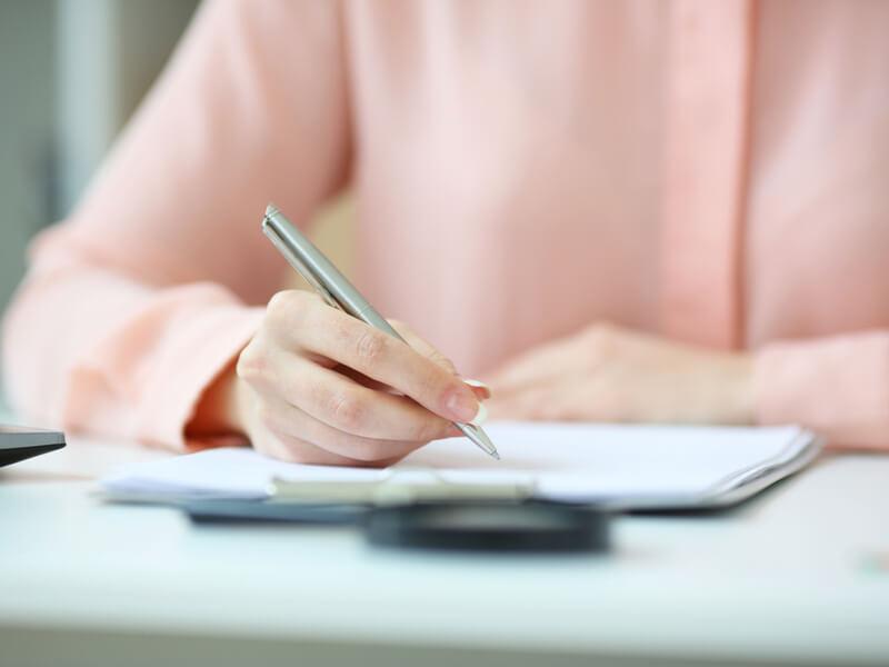 Nahaufnahme von den Händen einer Frau, die Dokumente prüft.