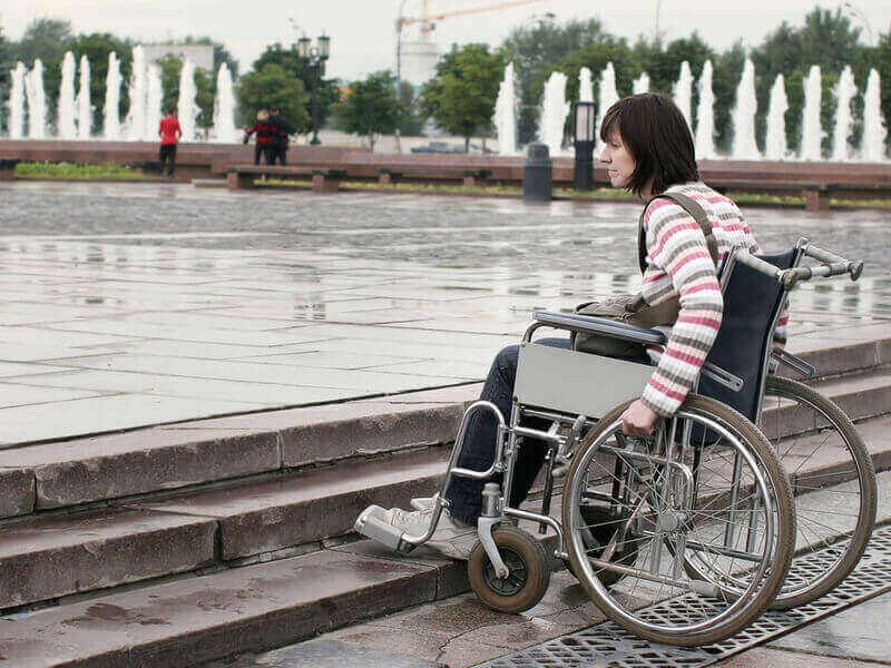 Erschwerte Teilhabe: Rollstuhlfahrerin vor Treppen