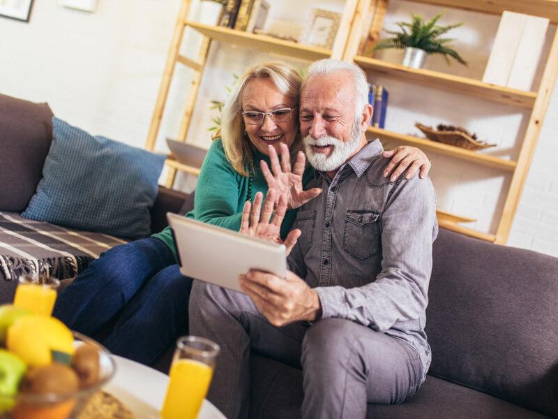Älteres Paar auf der Couch macht Videotelefonie per Tablet