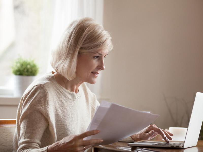 Ältere Dame mit Dokumenten in der Hand am Laptop