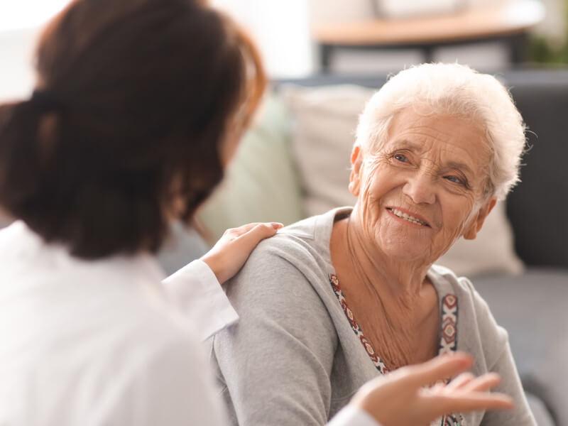 Ambulante Pflege: Pflegekraft legt ihre Hand auf die Schulter einer alten Dame