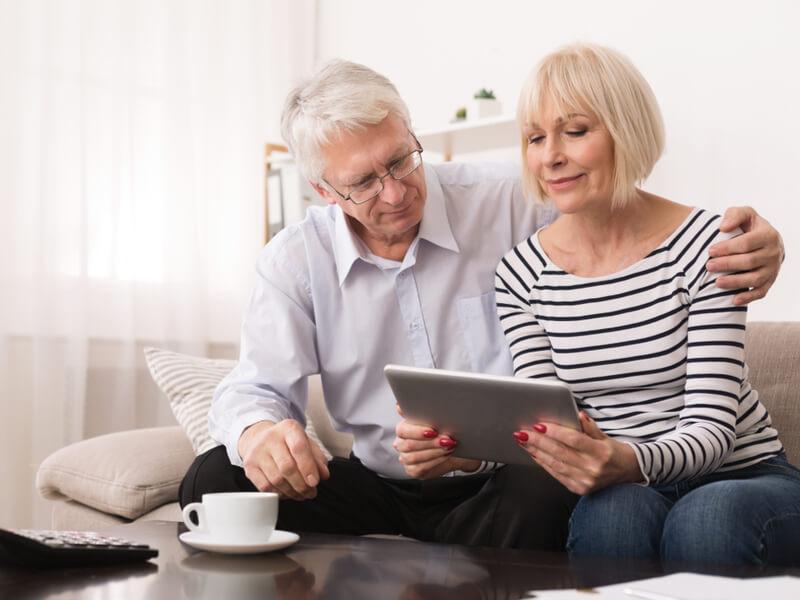 Älteres Paar sitzt mit einem Tablet auf dem Sofa