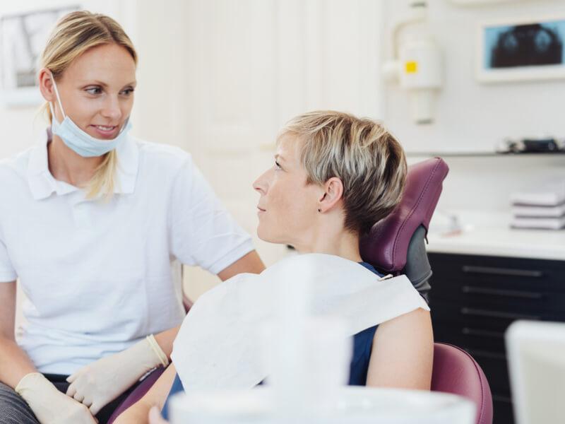 Patientin auf dem Zahnarztstuhl im Gespräch mit der Zahnärztin