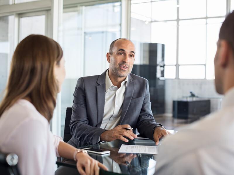 Bankangestellter im Gespräch mit einem Mann und einer Frau